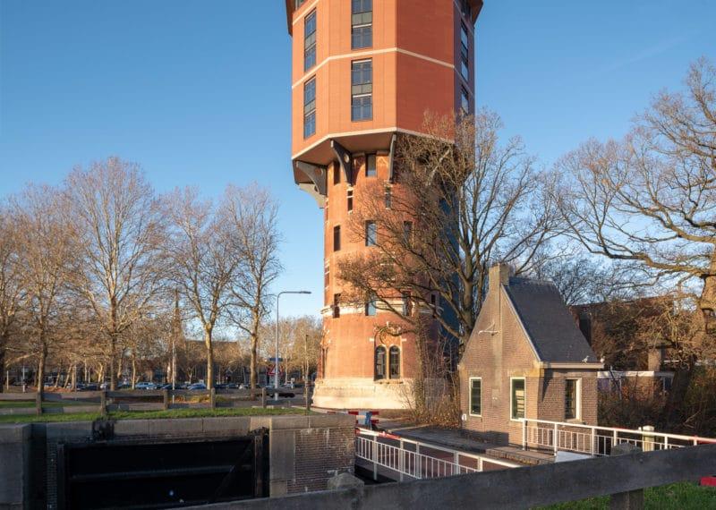 Zicht op Zwolse Watertoren met dijk en huisje op voorgrond