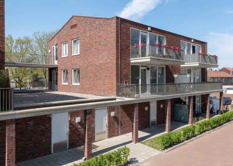 Foto van een roodbruin gebouw op dezelfde hoogte, met balkons en een overkapping