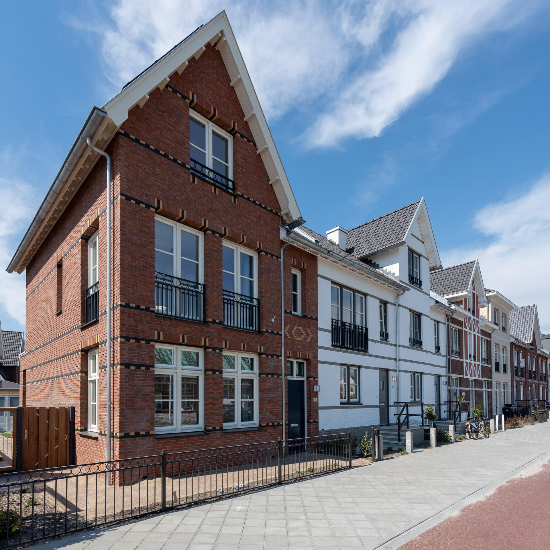 Rij nieuwbouwwoningen in negentiende-eeuwse stijl in verschillende kleuren en ontwerpen