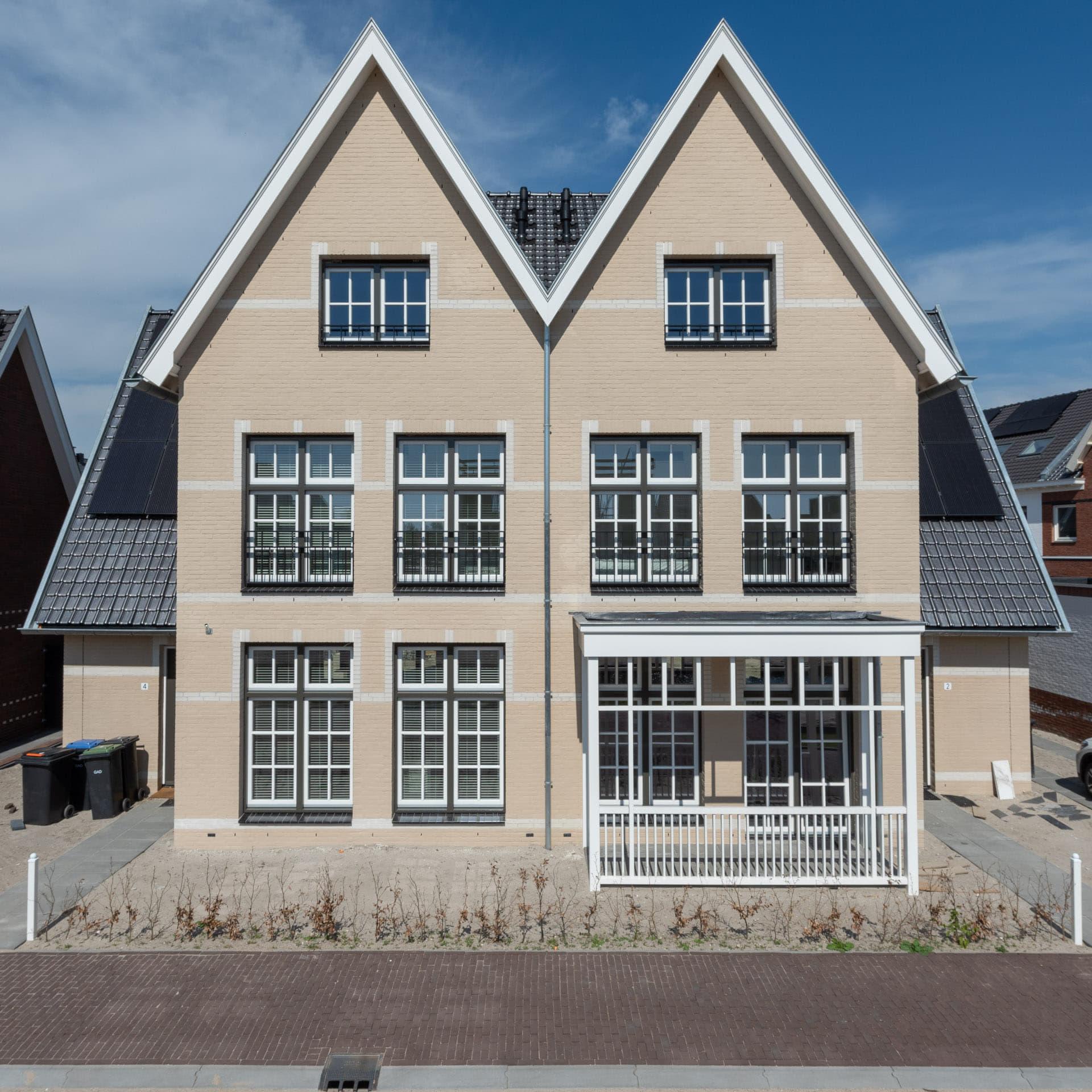 Twee-onder-een-kap woning van een lichte steen met twee puntige daken
