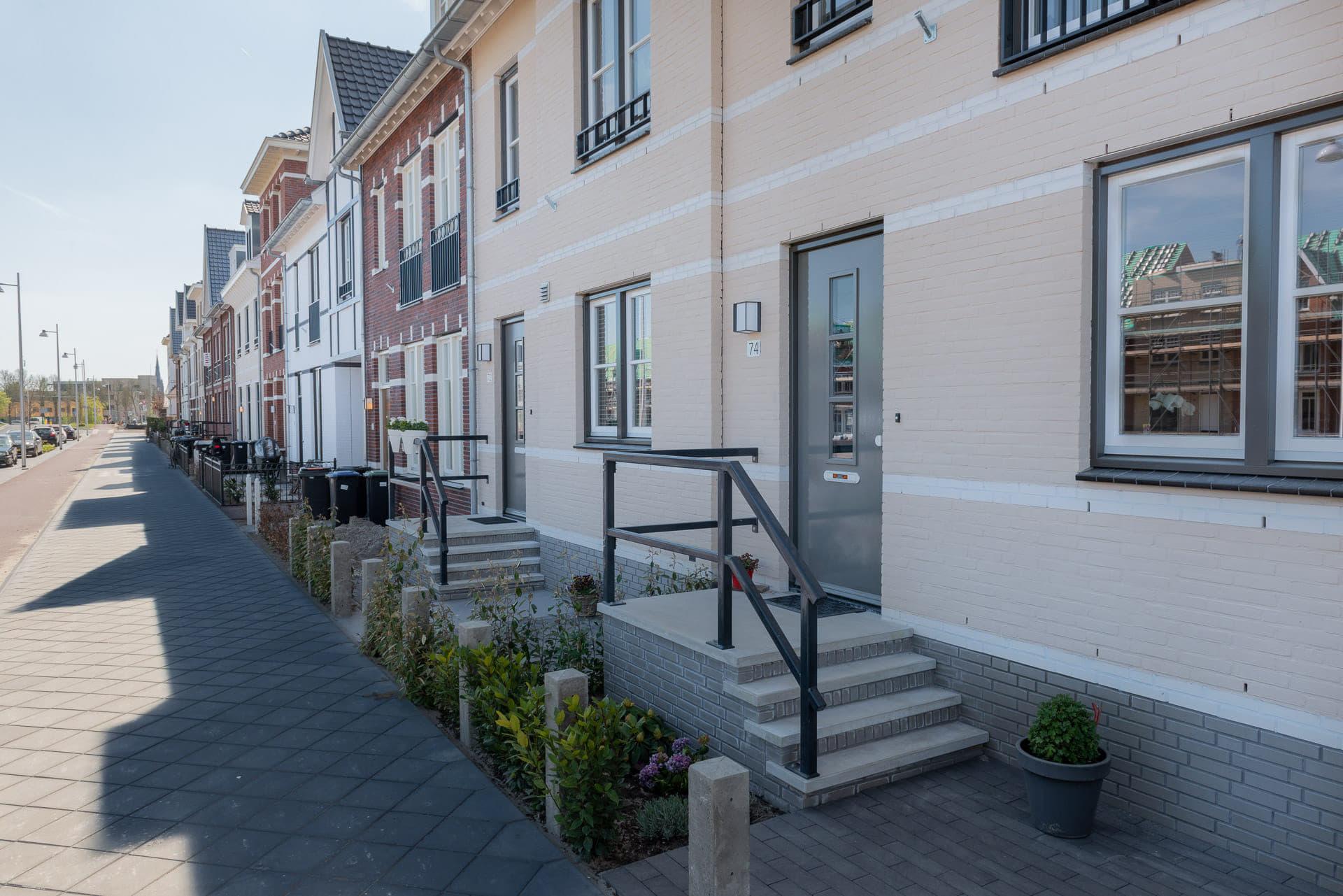 Een rij huizen vanaf de zijkant bekeken met op de voorgrond een trapje naar de voordeur