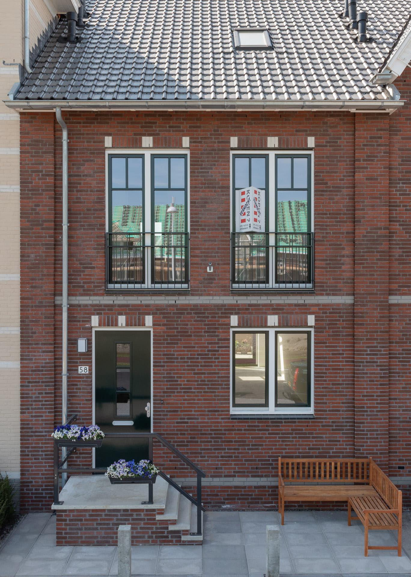 Gevel van rode steen met een voordeur met een trapje en drie ramen