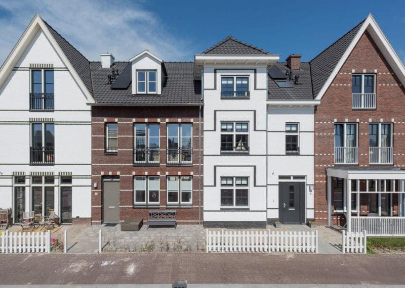 Rij van vier woningen in eind negentiende eeuwse stijl, maar nieuwgebouwd in verschillende kleuren wit en rood/bruin