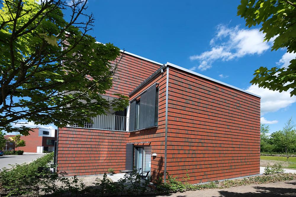 Zijaanzicht van een roodbruin gebouw met Architile tegels