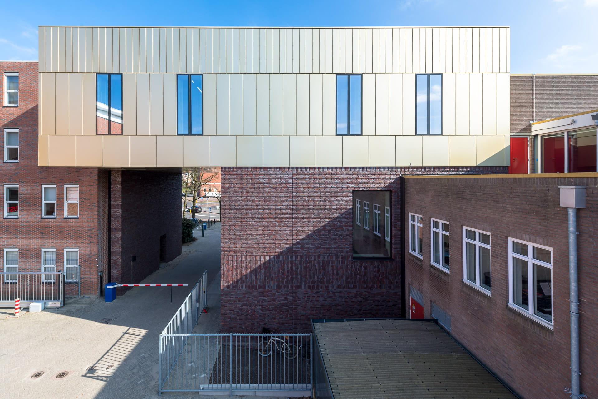Zicht op gevel van Conservatorium Groningen met onderste laag donkere stenen en bovenste gedeelte een lichte muur.