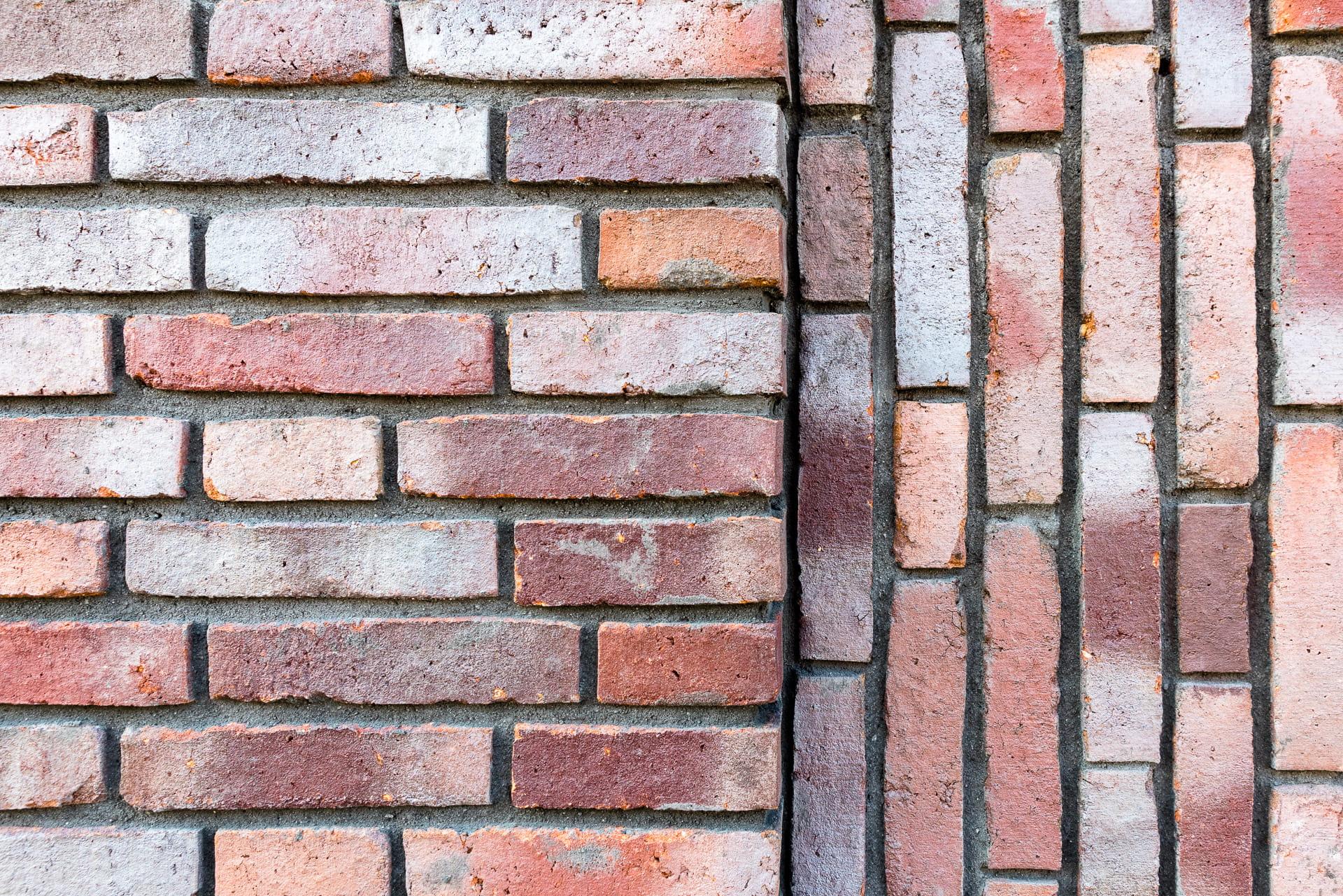 Closeup van een muur met verschillende lagen en een gedeelte horizontaal en verticaal gemetseld.