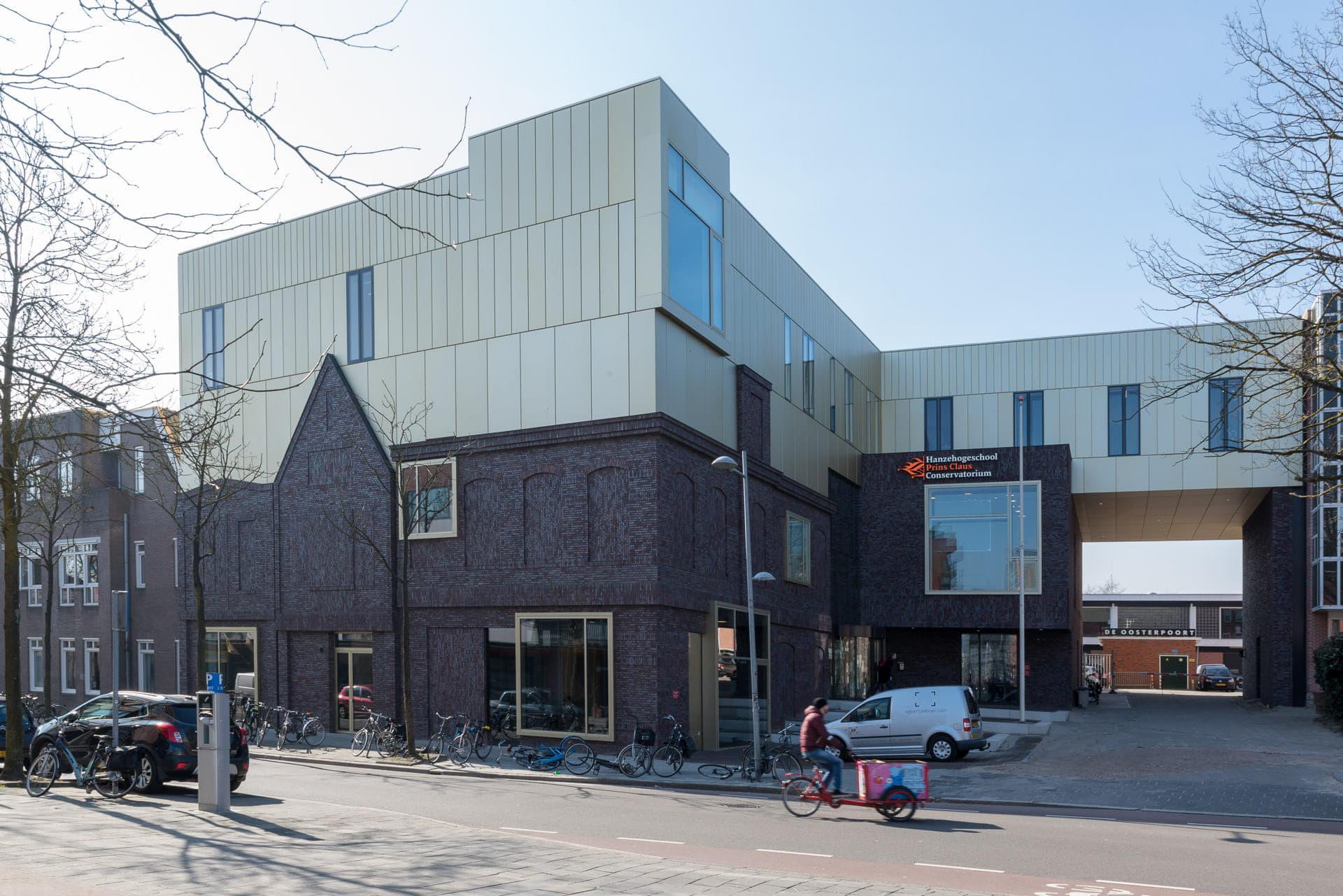 Prins Claus Conservatorium vanaf de hoek bekeken, met donkere bakstenen onder en lichte gevel boven.