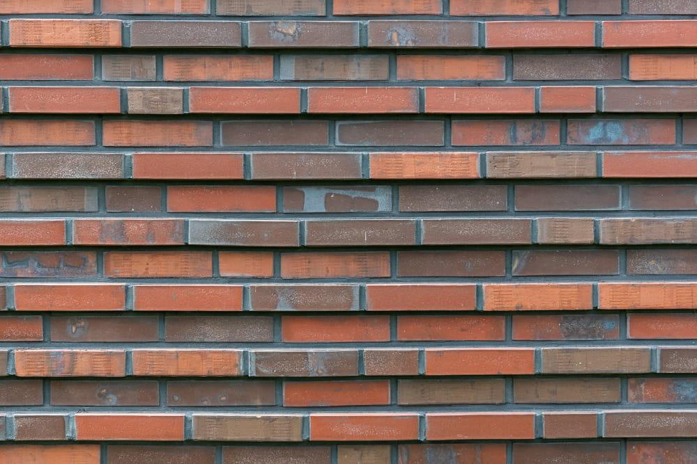 Muur met steenstrips die om en om uitsteken in rode en donkere kleur