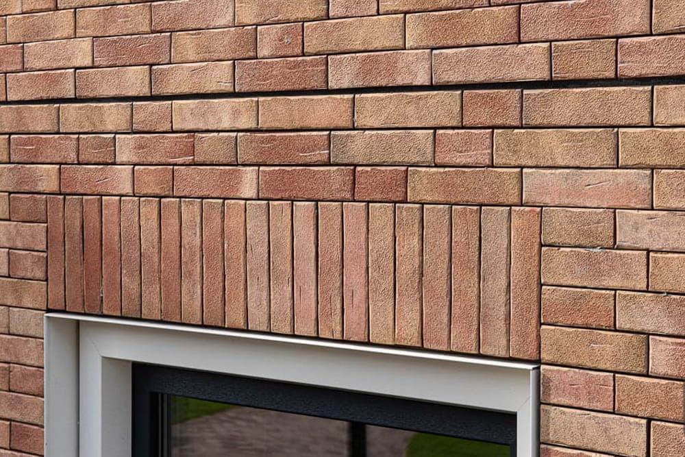 Muur van lichte steenstrips boven een raam met verticale steenstrips en horizontale steenstrips