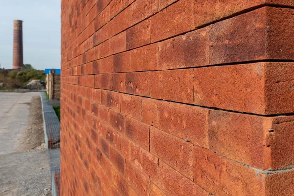 Rode muur met steenstrips met op de achtergrond een industrieterrein