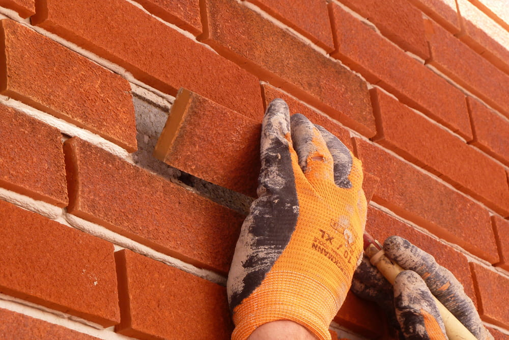 Handen met werkhandschoenen plakken een laatste steenstrip op een rode muur