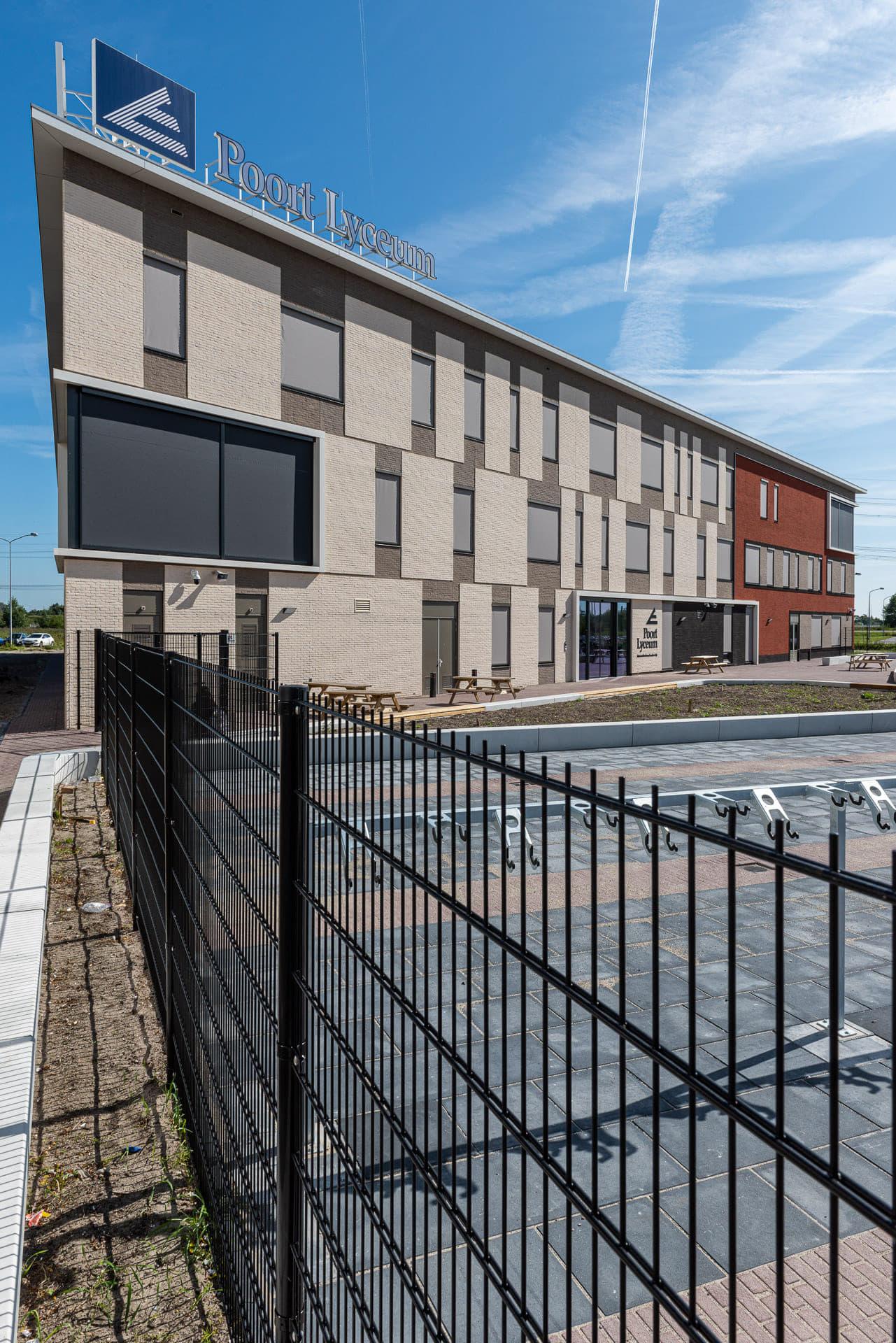 Schoolgebouw met een hek ervoor en Poort Lyceum letters op het dak