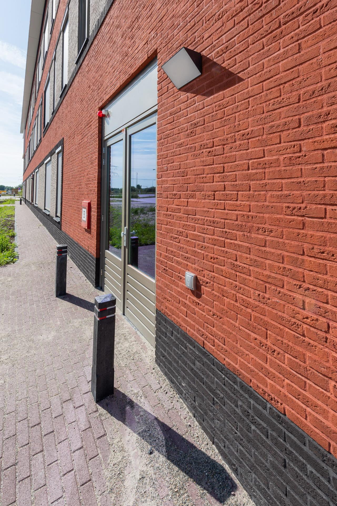Zijkant van een rode gevel met een deur en paaltjes ervoor
