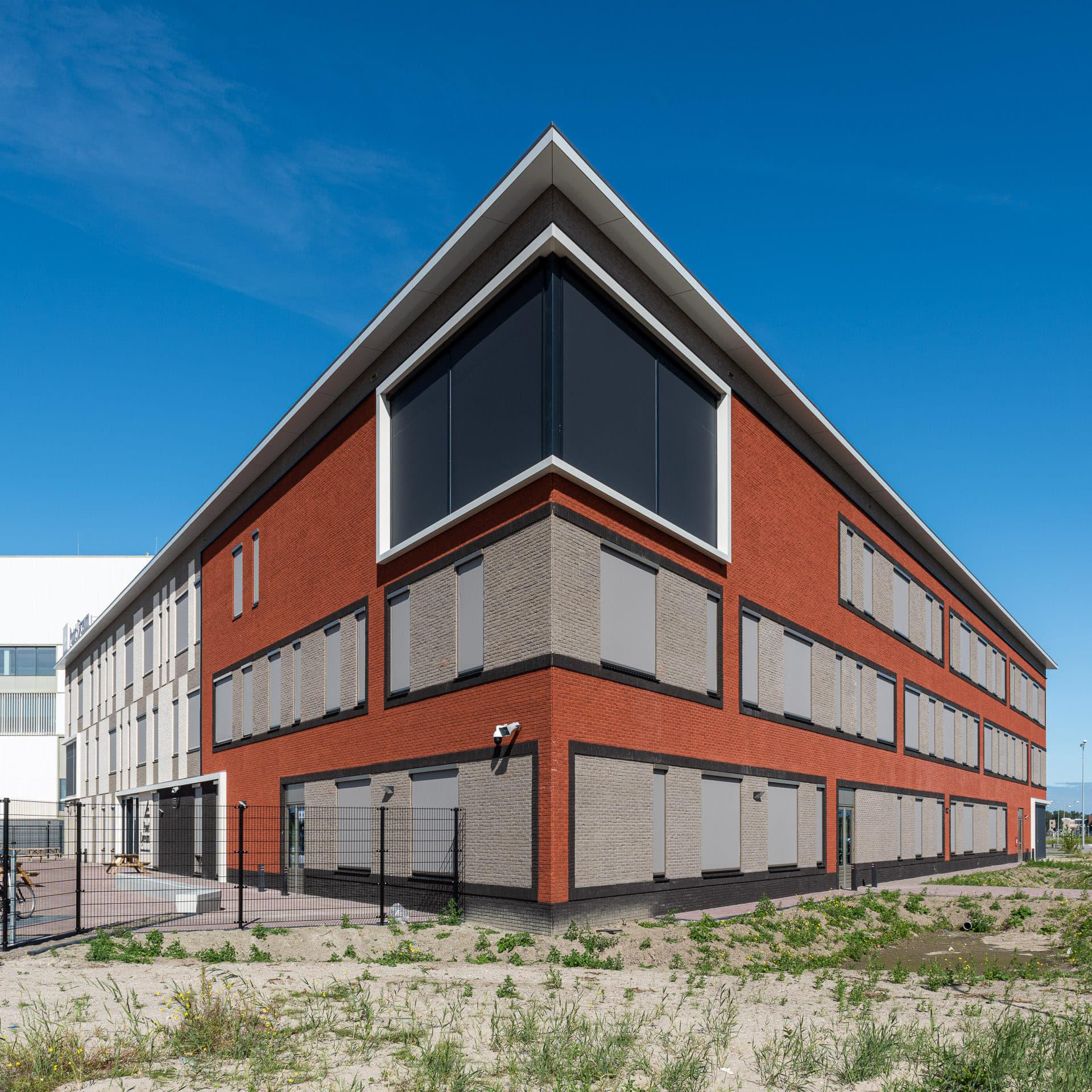 Hoek van een gebouw met rode en lichte vlakken, met groen en zand op de voorgrond tegen een blauwe lucht