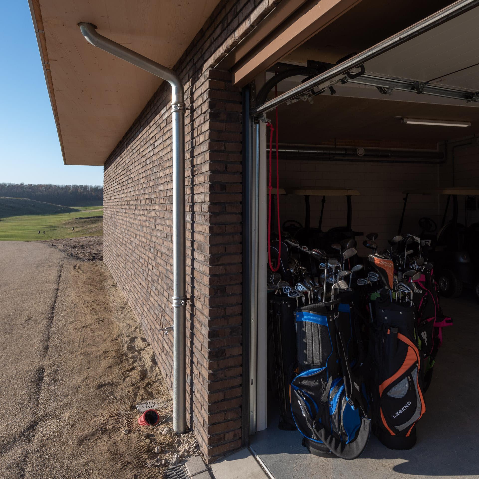 Zijkant een gebouw met op de achtergrond een golfbaan