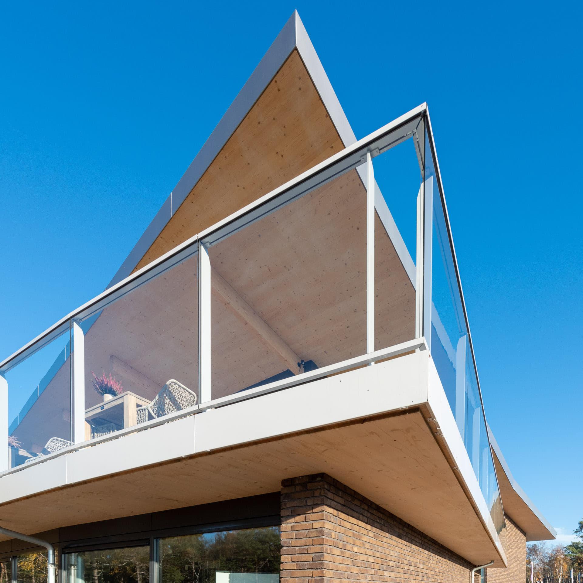 Punt van een strak dak met balkon op de voorgrond