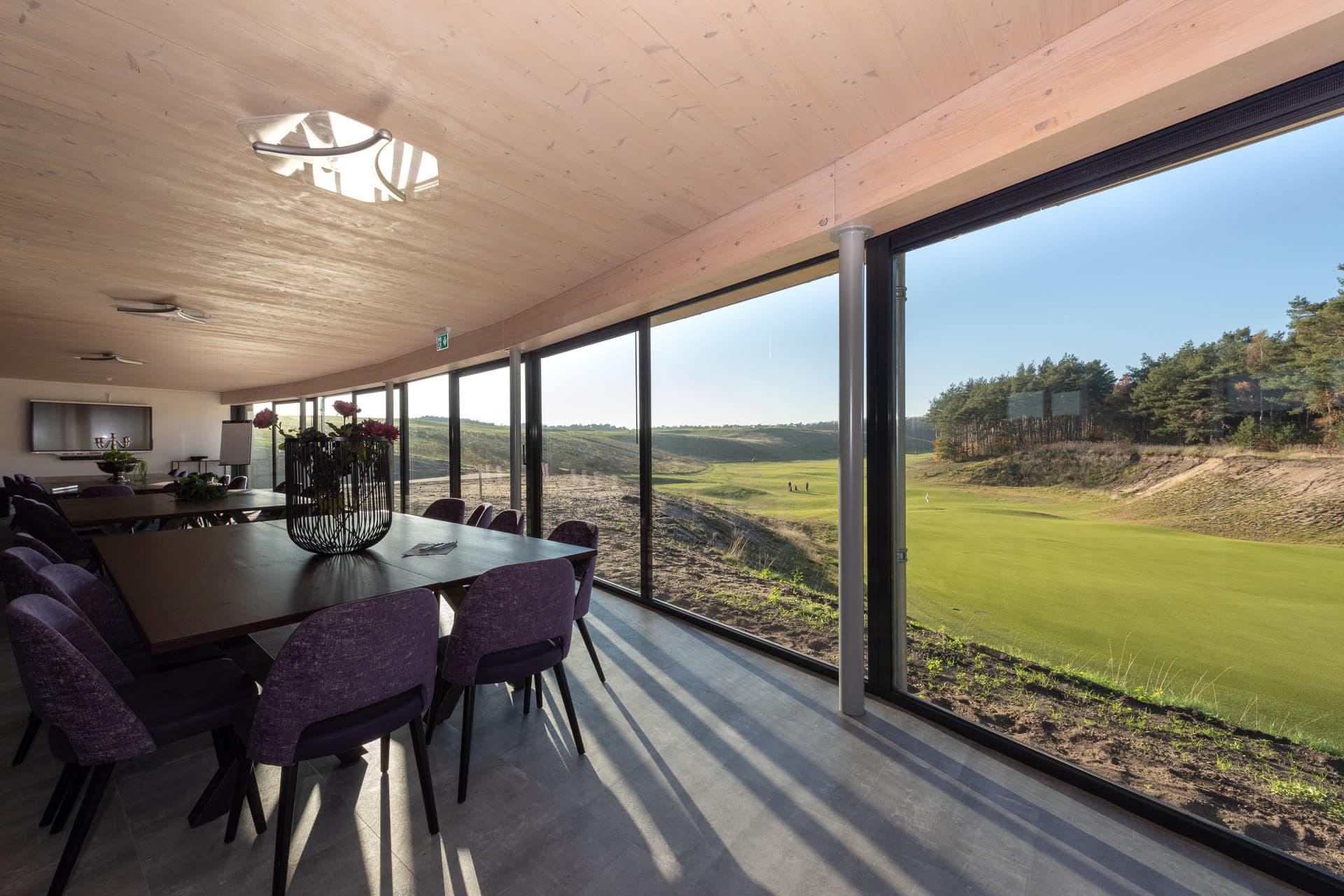Uitzicht door grote ramen op een golfterrein