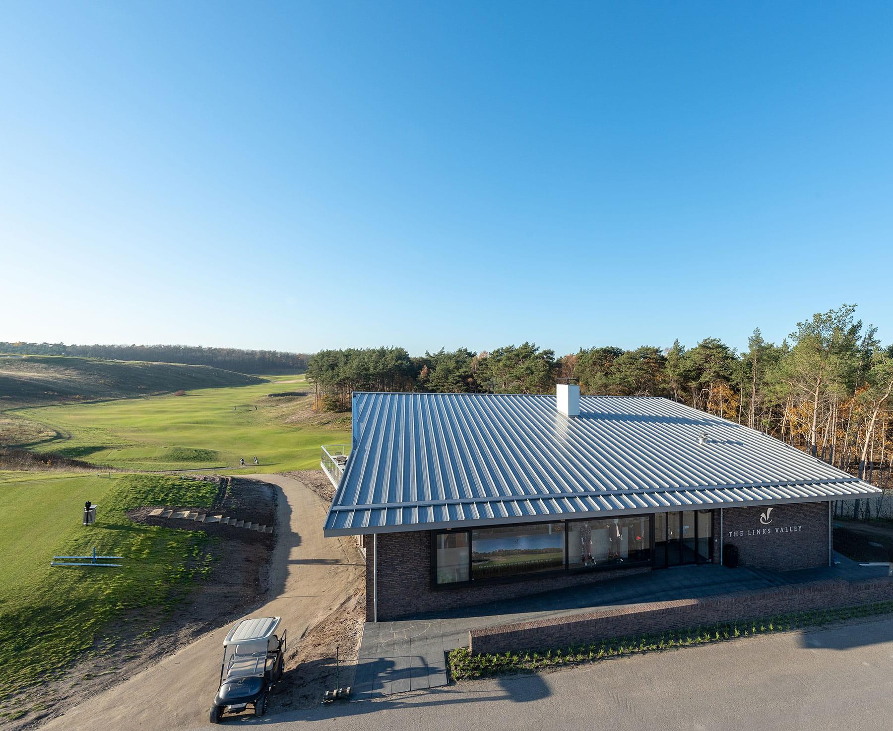 Zicht op een golfbaan met op de voorgrond een gebouw met een schuin dak