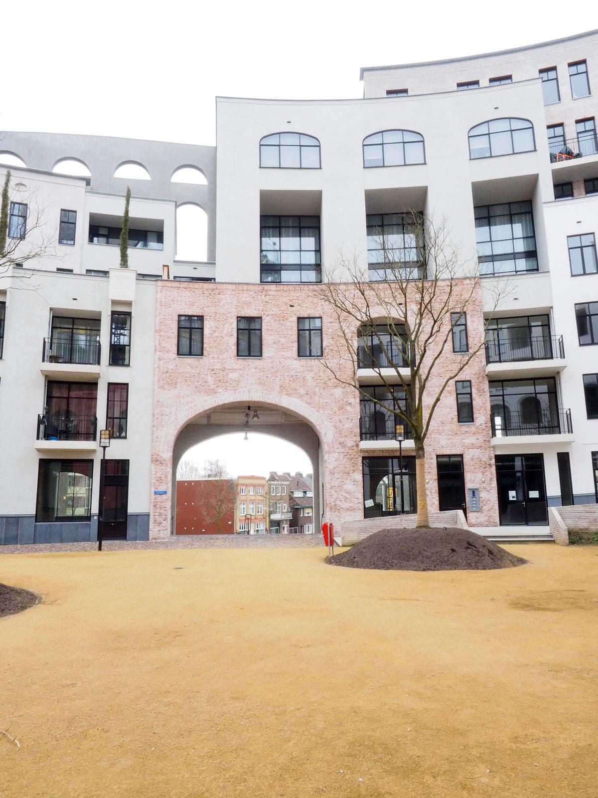 Zicht op een halfronde rij witte gebouwen met een rode poort in het midden en een boom ervoor