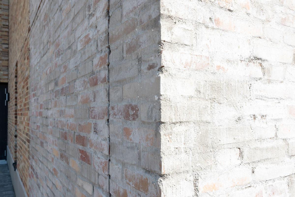 Hoek van een witte gechipperde muur