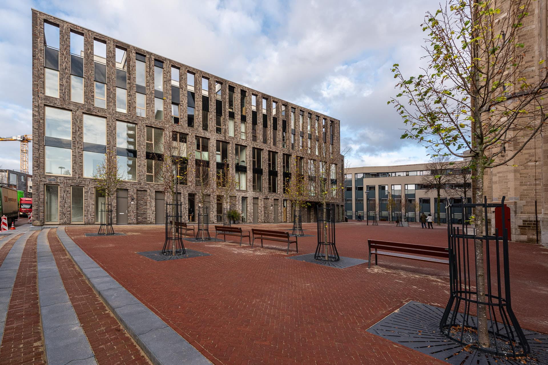 Zijkant van lichte gevel met grote ramen en plein op de voorgrond