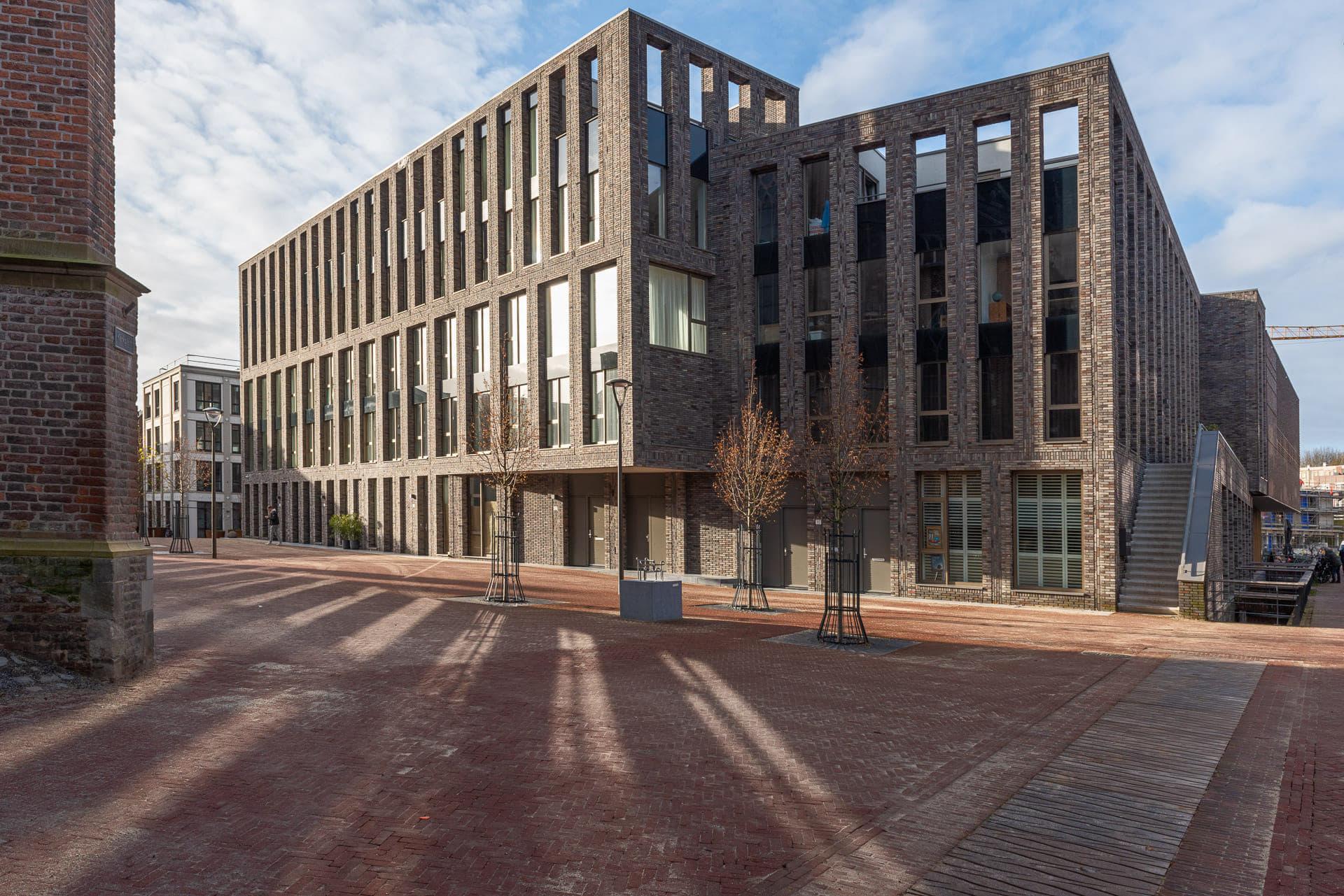 zijaanzicht van een grote partij ramen en lijnen in de gevel met op de voorgrond een plein