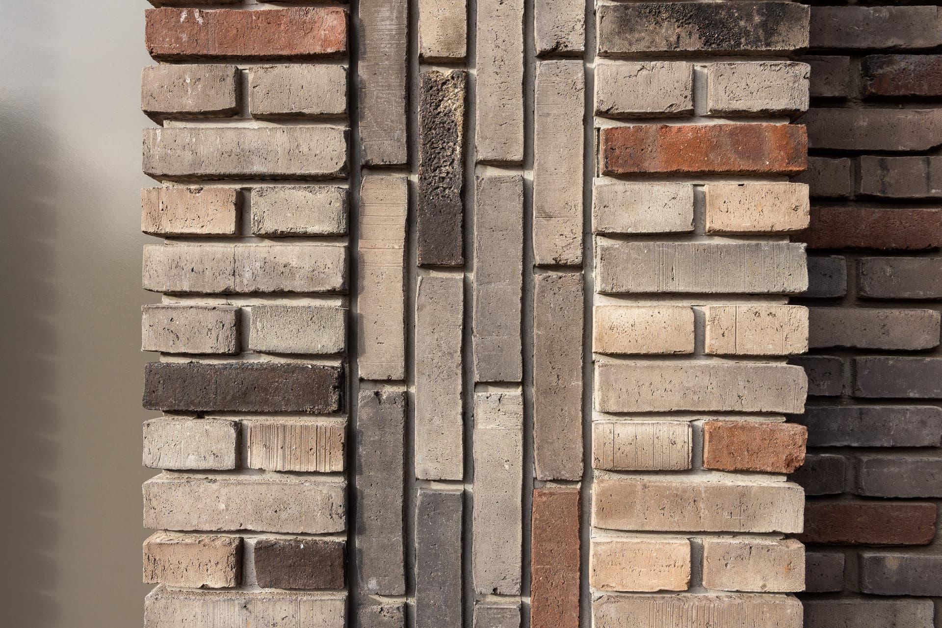 detail van een muur met verticaal en horziontaal metselwerk van gekleurde lichte stenen
