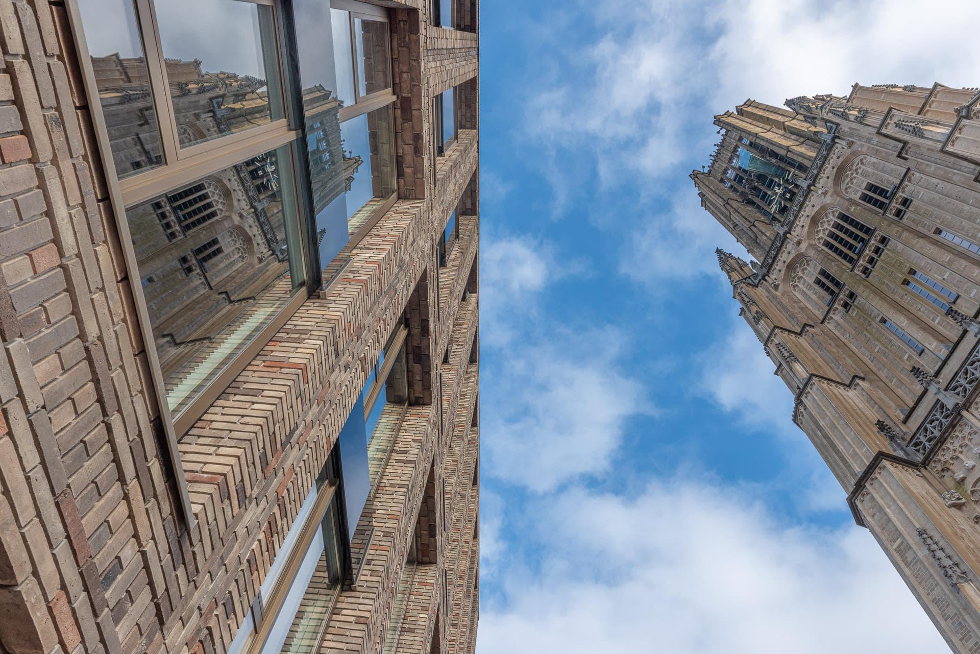 blik omhoog naar de blauwe lucht met rechts een oude kerktoren en links een gebouw waarin de toren weerspiegelt in de ramen