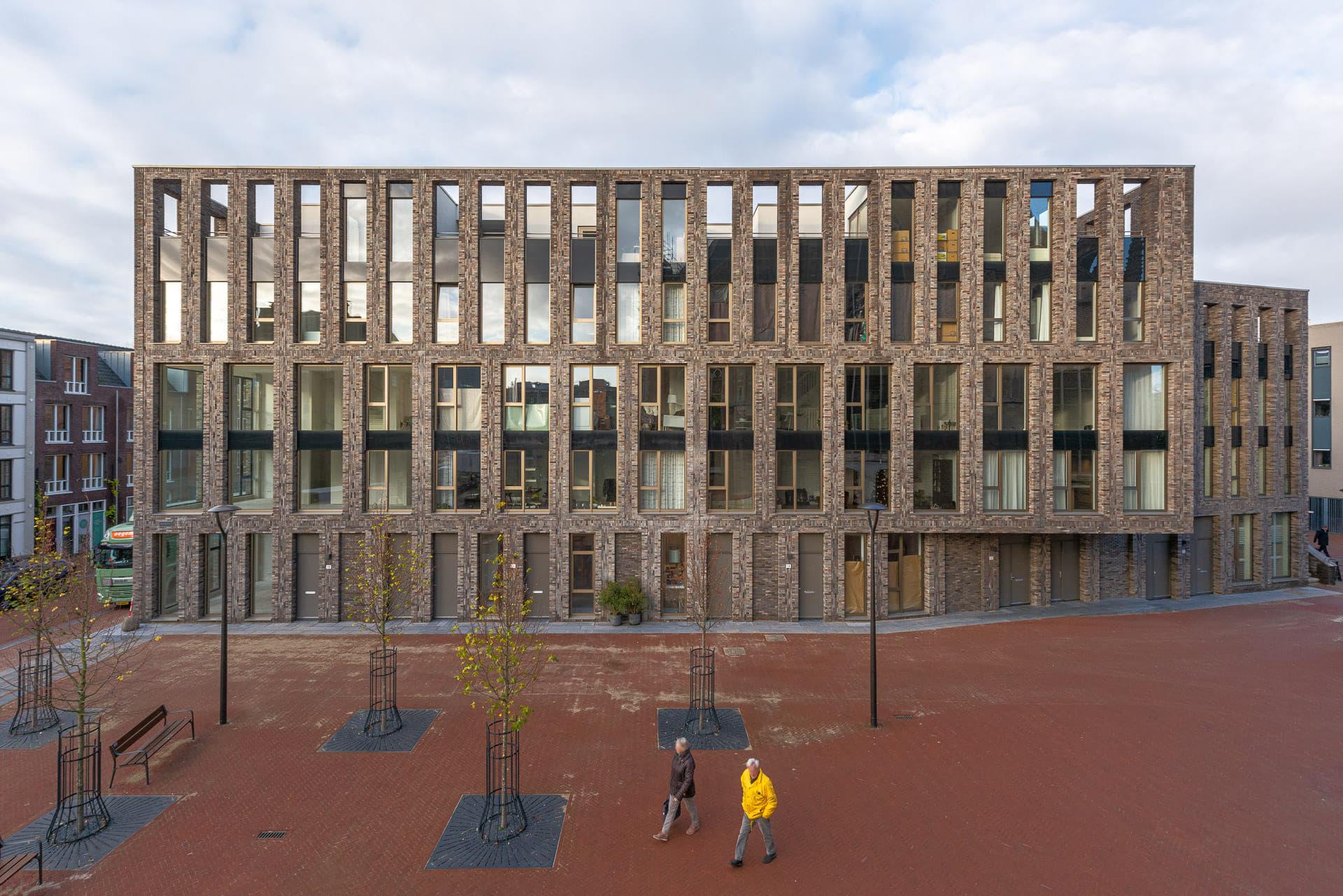 Vooraanzicht van lichte gevel met grote ramen en plein op de voorgrond