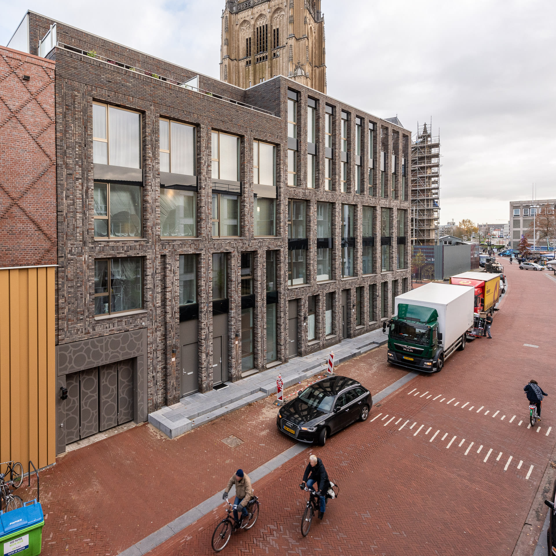 Gebouw met lichte gevel met op de voorgrond een straat met fietsers en auto's en busjes