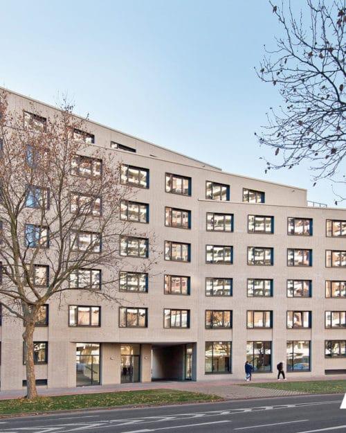 Licht gebouw met veel ramen met daarvoor een straat, ter illustratie van het gevelsysteem a-brick