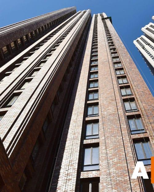 Torens met bruine keramische strips van onderen gefotografeerd tegen een blauwe lucht