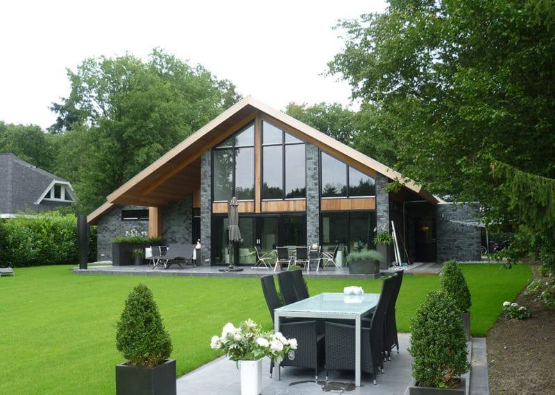 Vrijstaande woning met donkere ClickBrick en houtkleurige accenten met een tuin op de voorgrond