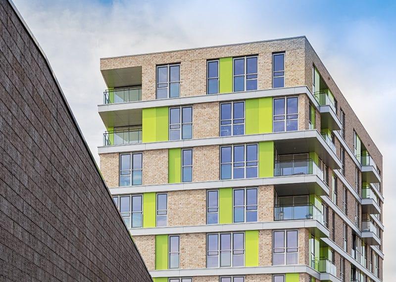 Gevel met ClickBrick, ramen en groene elementen tegen een blauwe lucht