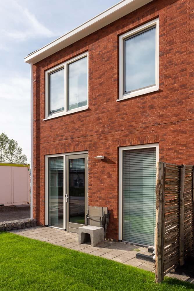 Huis met rode gevel en ramen en een stukje gras ervoor op de Loskade
