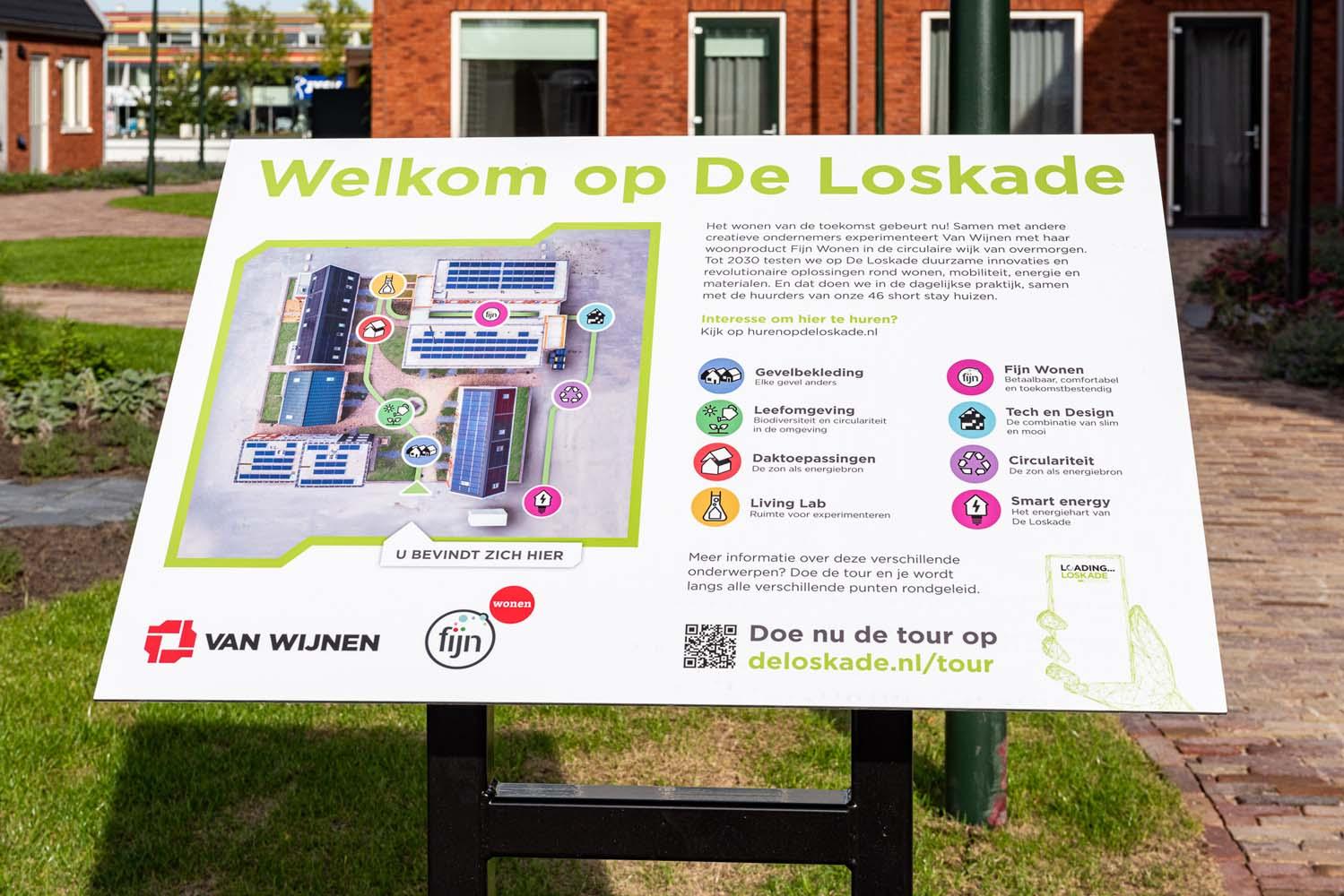Bord met uitleg over circulair bouwen en leven op de Loskade in het gras van het pleintje