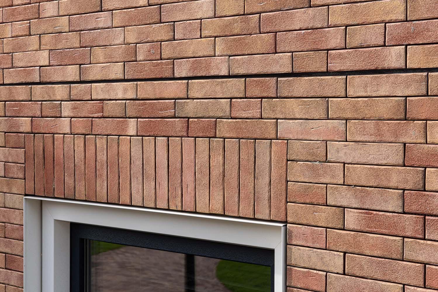 Muur met steenstrips en een rollaag boven het raam