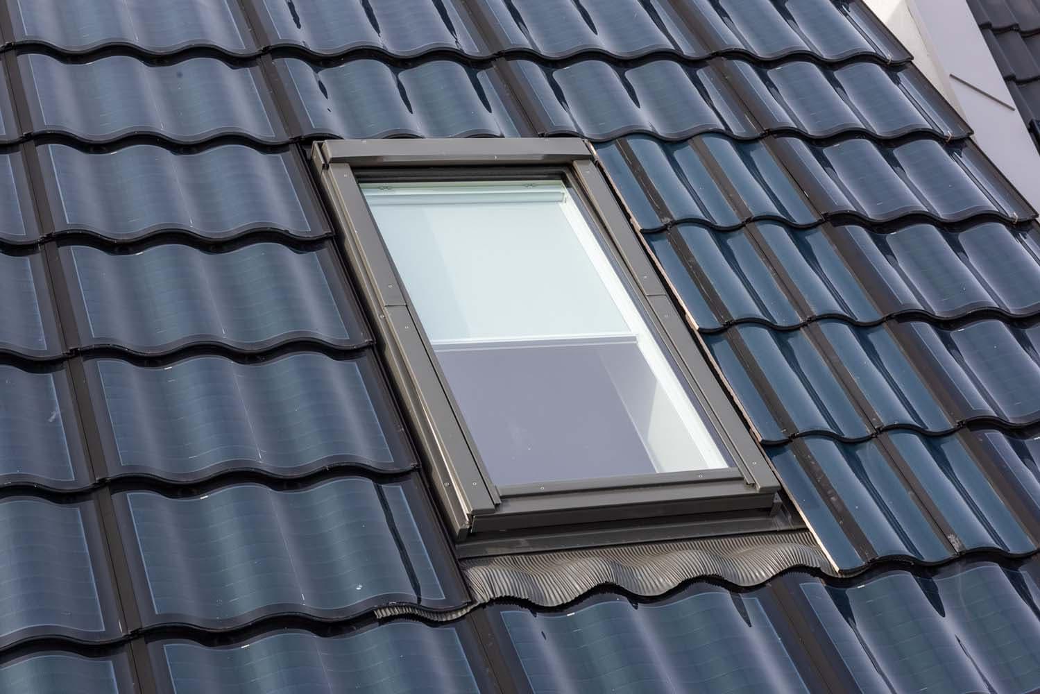 Zwart dak met zonnepanelen die eruit zien als dakpannen en een raam in het midden