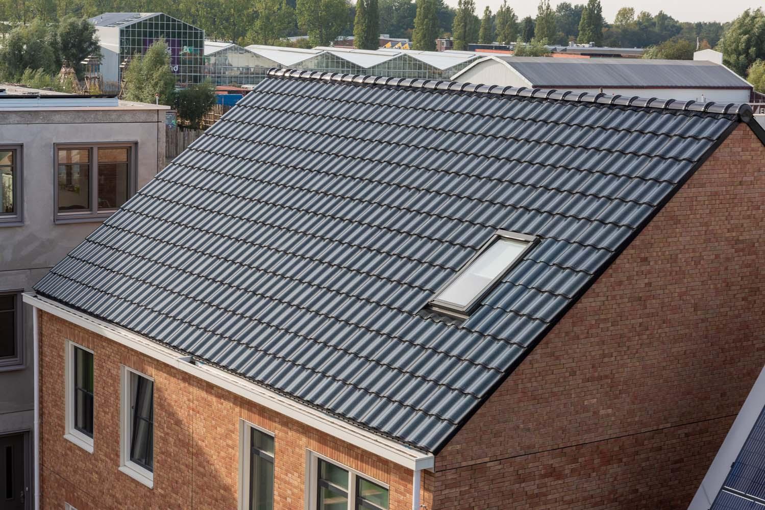Dak van een twee-onder-een-kap woning met dakpannen van zonnepanelen op de loskade