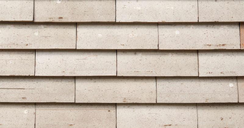 Detail van een lichte muur met grote sidings van het gevelsysteem Pantheon Nordic die gepotdekseld zijn gemonteerd