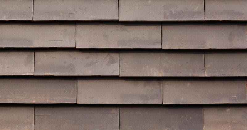Detail van een donkere muur met grote sidings van het gevelsysteem Pantheon Nordic die gepotdekseld zijn gemonteerd