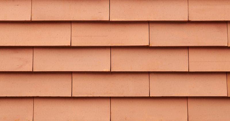Detail van een oranje getinte muur met grote sidings gevelsysteem Pantheon Nordic die gepotdekseld zijn gemonteerd
