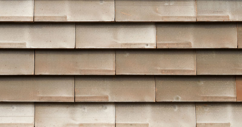 Detail van een grijsbruine muur met grote sidings van het gevelsysteem Pantheon Nordic die gepotdekseld zijn gemonteerd