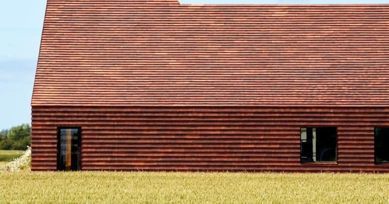 Zijaanzicht van een rood gebouw met ervoor een groen veld