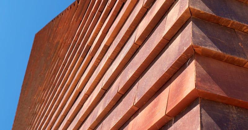 Detail van een rode muur met grote rode sidings tegen een blauwe lucht