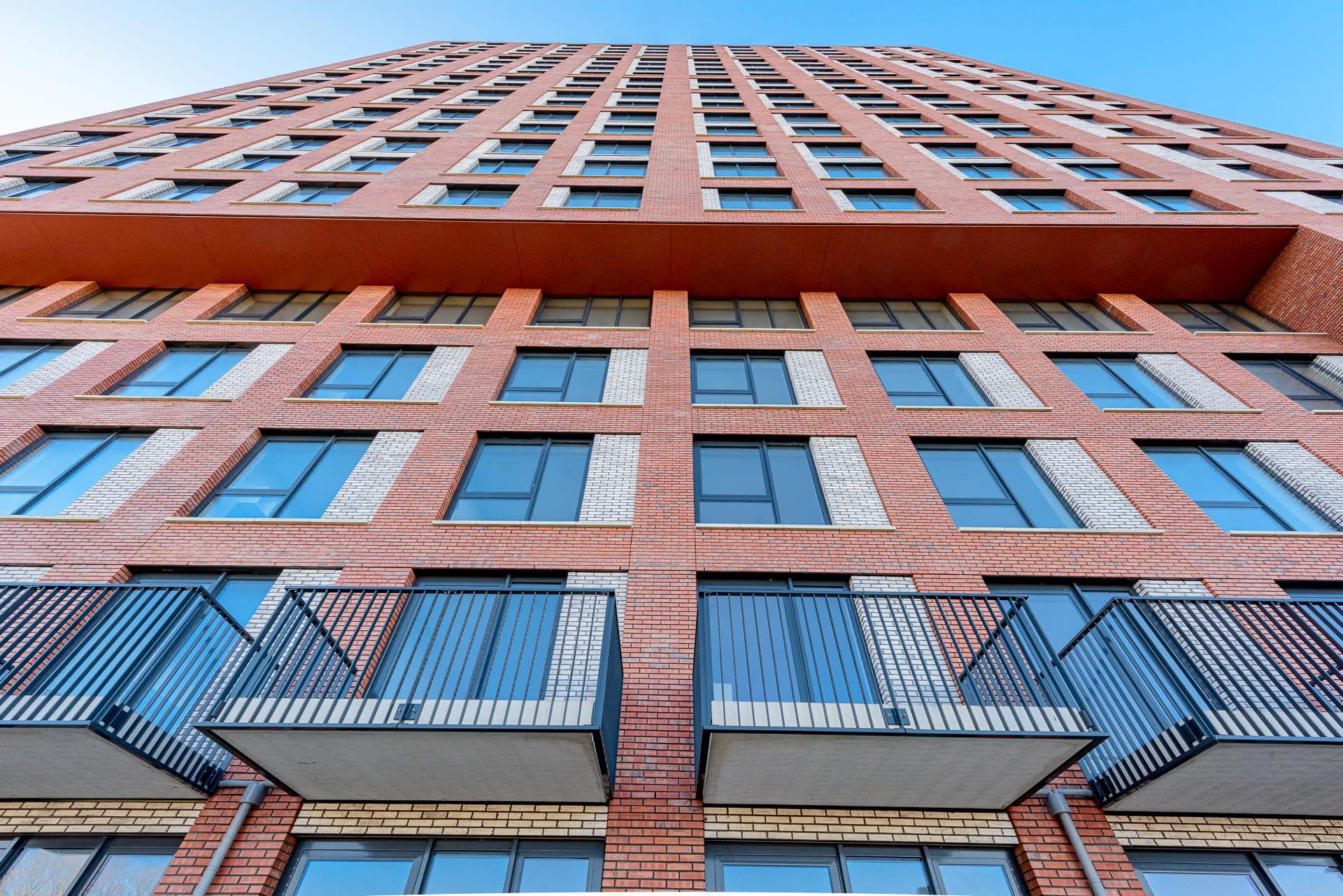 Gevel van een toren van onderen naar boven bekeken met balkons onderop