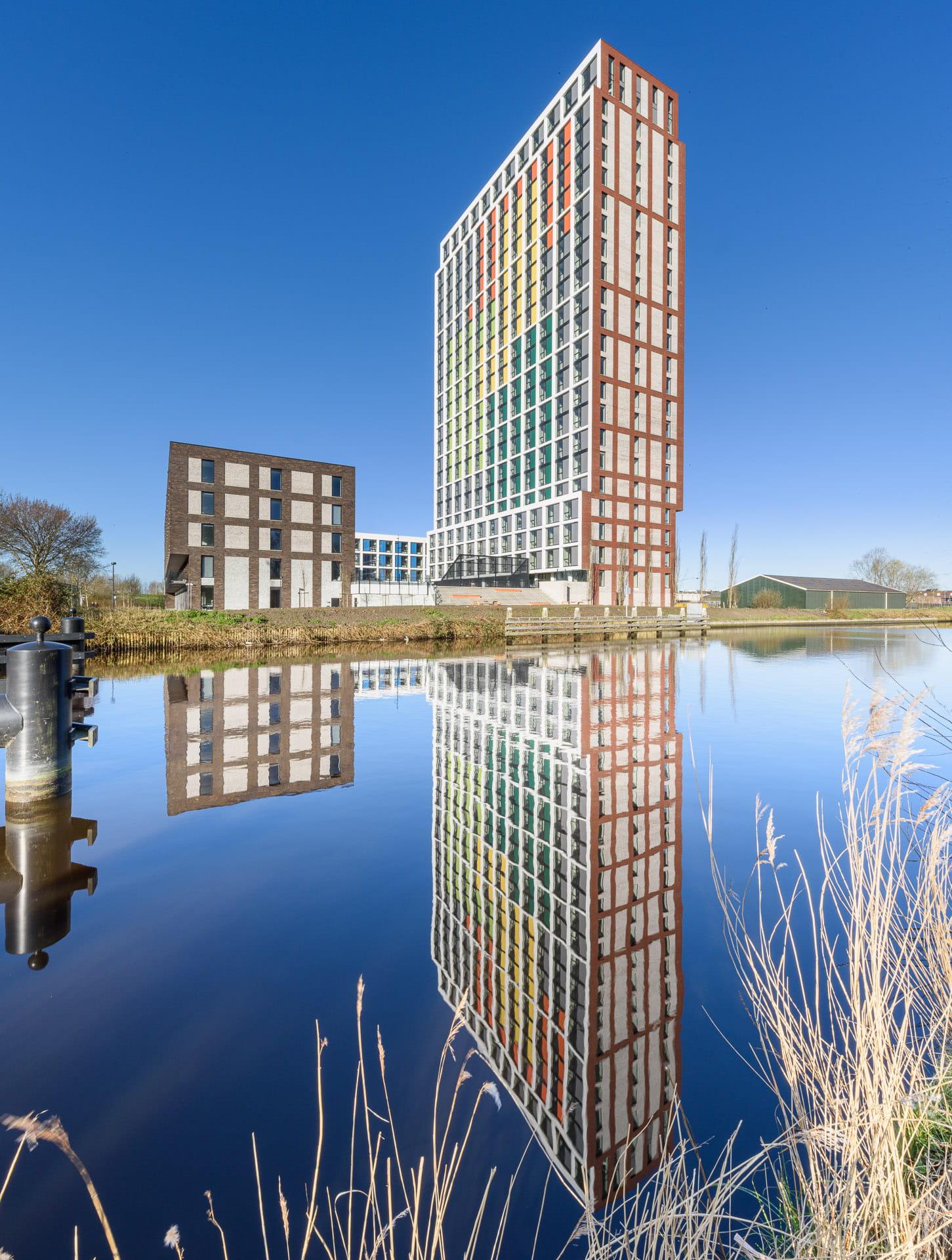 Een toren van rode en witte vlakken baksteen en gekleurde vlakken tegen een blauw lucht en op de voorgrond water