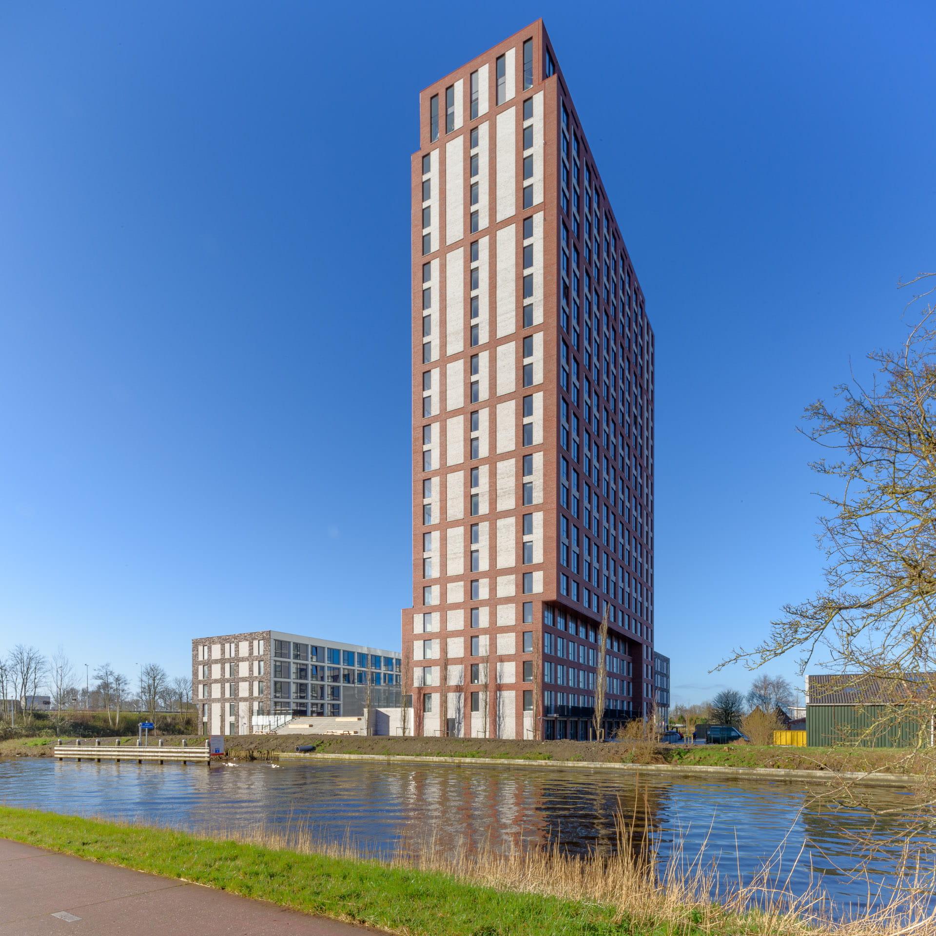 Een toren van rode en witte vlakken tegen een blauw lucht en op de voorgrond water