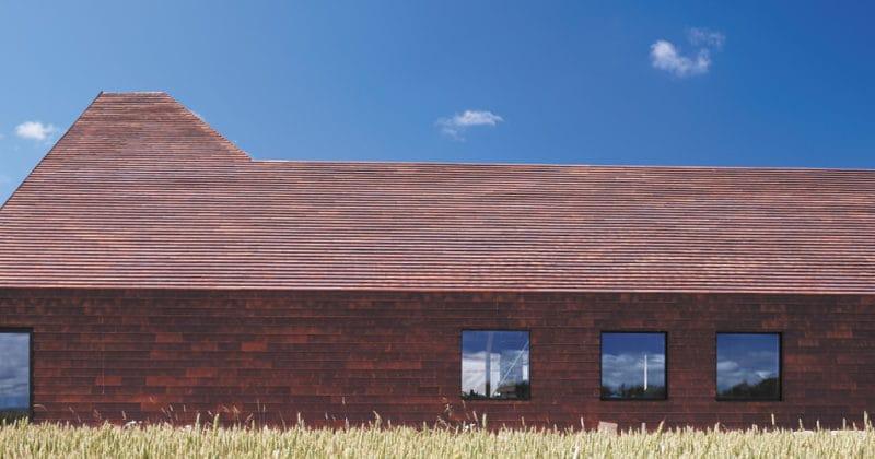 Langwerpig gebouw in een graanveld, geheel in het keramische gevelsysteem Pantheon Nordic