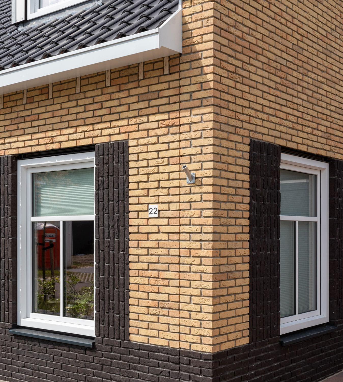 Hoek van een huis met lichte bakstenen en donkere dakpannen